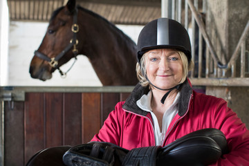 Portrait Of Mature Female Owner Holding Saddle In Stable With Horse