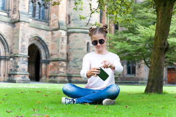 Young teenage girl with smartphone sitting in Glasgow University garden