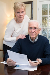 Portrait Of Concerned Senior Couple Reviewing Domestic Finances