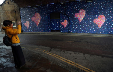 A woman takes a photograph of a mural, by British-born Australian artist James Cochran, painted to commemorate the victims of the London Bridge attack, in London