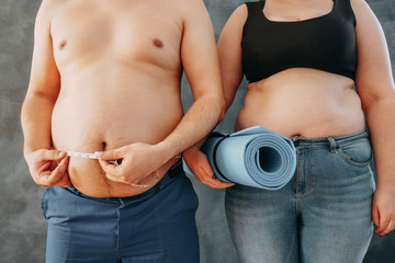 Overweight couple with measure tape and yoga exercise mat. Family weight losing
