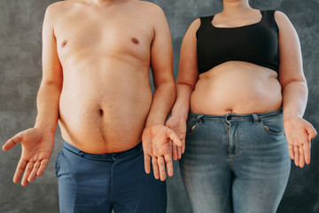 Overweight couple in perplexity, bewildered. Dieting, weight losing and health care concept