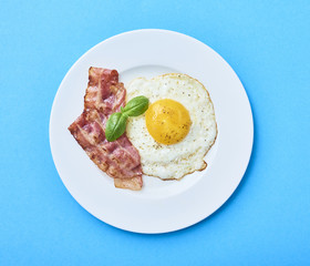 tastu fried egg in plate with bacon