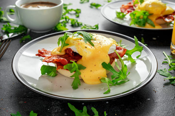 Eggs Benedict on english muffin with crispy bacon, wild rocket salad and hollandaise sauce.