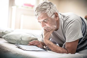Using digital tablet in bed.