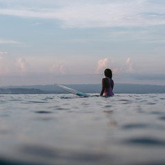 silhouette of female surfer sitting on surfboard in ocean at sunset