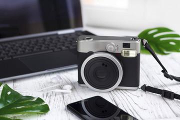 Laptop, leaves, retro camera, mobile phone on white