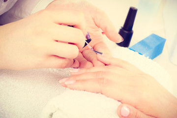 Close up of client and manicurist hands.