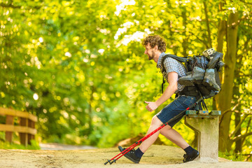 man hiker with backpack resting on bench in forest trail