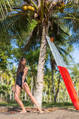 attractive young girl in swimsuit dancing near palm with surfboard