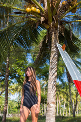 young surfer posing with surfboard near palm tree
