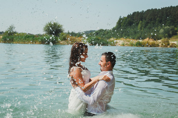 Wedding couple is hugging in azure blue lake splashes of water. Beautiful bride in puffy dress and groom are having fun. Summer passion crazy emotions photo on the seaside. Wet wedding clothes.