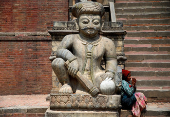 A woman begs for alms as she sits on the stairs of Nyatapola Temple in Bhaktapur