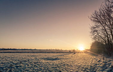 Countryside sunrise over a frozen field