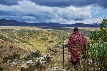 Traditional Masai looks over crater rim moutain