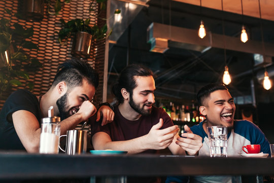 Happy arabian young men hanging in loft cafe. Group of mixed race people having fun in lounge bar