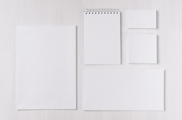 Corporate identity set of blank white stationery on soft white wood board. Template for branding, business presentations and portfolios.