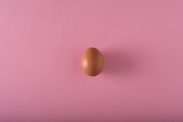 Minimalism. one egg in the center on a light pink background
