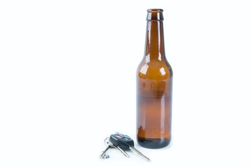 Drink don't drive concept. Glass bottle with Car keys on isolated white.