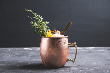 Cold orange Moscow mule cocktail in copper mug. Selective focus.