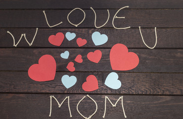 forming the word: W love u MOM on wooden background