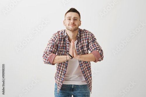 8f04c9b08367 Indoor shot of positive emotive young guy in glasses bowing while greeting  someone in asian style with clasped palms near chest