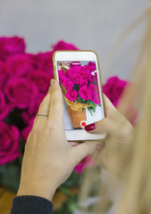 Girl shoots on your smartphone beautiful rustic bouquet in the friend's hands