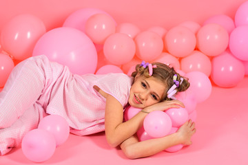 little girl in a pink pajamas plays with balloons.