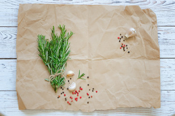 Bunch of rosemary with garlic and spices on wrapping paper