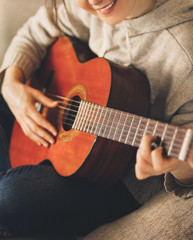 Young woman musician guitarist playing guitar at home