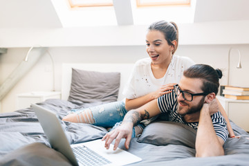 Young couple watching a movie on their laptop in bed