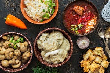 Russian variety of dishes, borsch, dumplings, pickled mushrooms, sauerkraut. Russian food on a rustic background, top view.