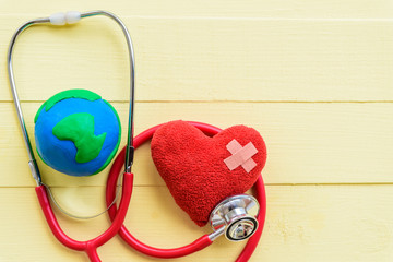 World health day, Healthcare and medical concept.  Stethoscope with handmade globe and Red heart on Pastel white and yellow wooden background.
