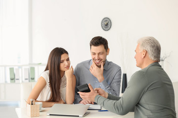 Young couple discussing pension plan with consultant in office