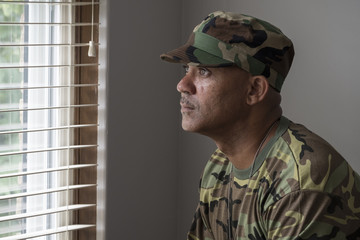 Portrait of a black man in fatigues looking out a window