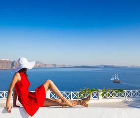 Santorini travel tourist brunette woman in red dress visiting famous white Oia village.
