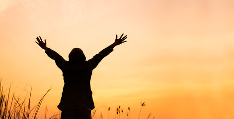 Asian woman enjoying nature and freedom , Women are lifting their hands up in the sky at sunset