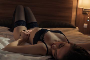 sexy girl in black lingerie lies in bed. view from above