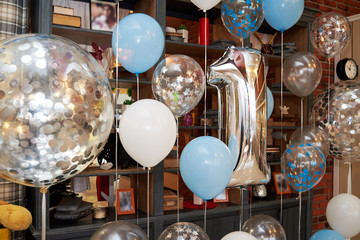 Anniversary or birthday photo zone with white, blue and transparent balloons, free space. Colorful balloons background, one year. Number one. Holiday concept