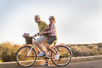 senior couple move with a bicycle together outdoor like childrens