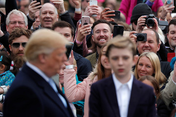 Guests take pictures as U.S. President Donald Trump and his son Barron attend the annual White House Easter Egg Roll event on the South Lawn of the White House in Washington