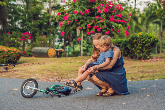 The boy fell off the bicycle, his mother pastes a plaster on his knee