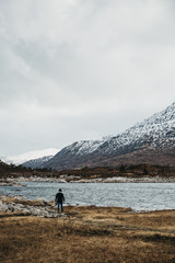 Man walking by scowcapped mountains and Loch Duich in Scottish Highlinds, Scotland, in spring.