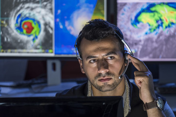 Meteorologist monitoring storms on his computer screens, close up shot Fotomurales