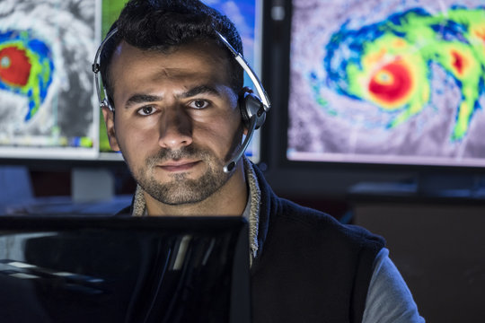 Portrait of a Meteorologist monitoring storms on his computer screens, close up shot