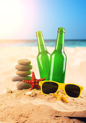 Two cold beer bottles on sandy beach