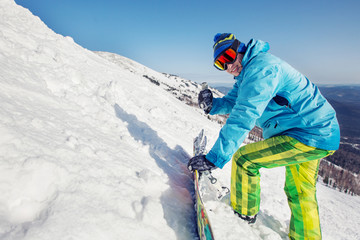 Guy have fun and playing on snow mountain top, showing thumbs up. Snowboard, freeride and winter holiday