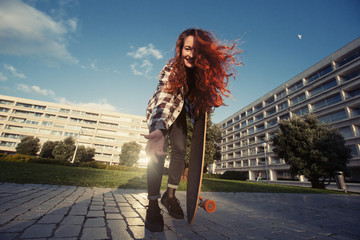 Young happy female with skate longboard outdoor