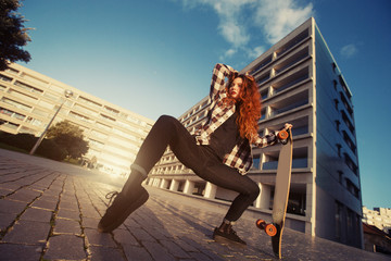 Young happy female have fun with skate longboard outdoor