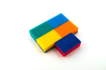 Разноцветные губки для мытья и чистки, четыре уложены вверх поролоном, одна – тонким абразивным слоем.